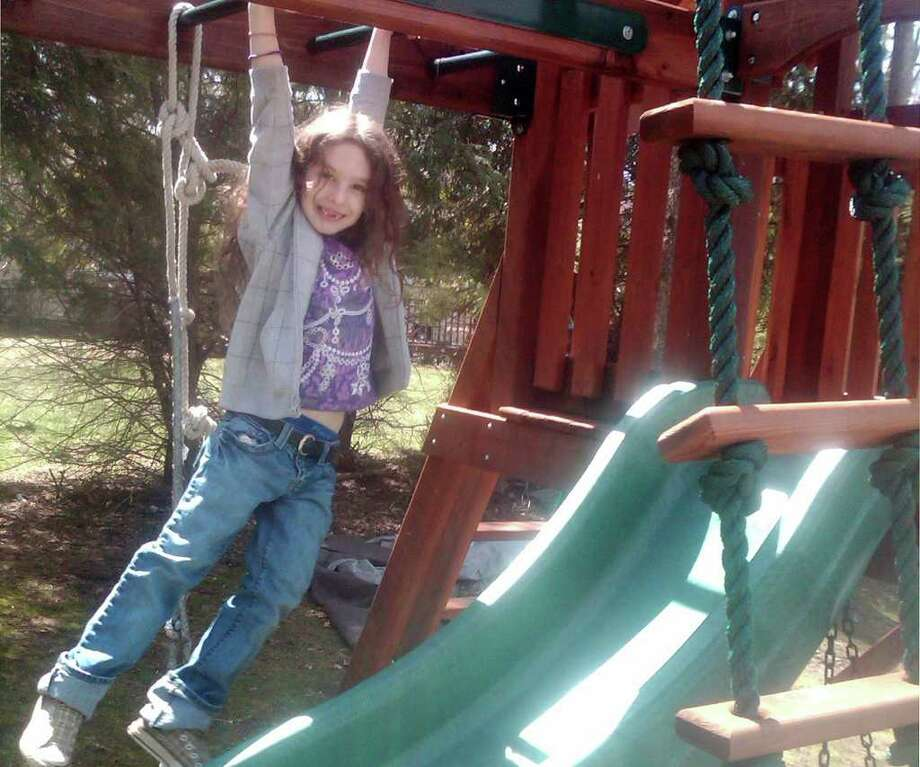Lynnea Moskowitz, daughter of Cary Moskowitz, hangs out on the monkey bars of her swing set in her Sturges Highway yard. The Zoning Board of Appeals on Tuesday approved a stipulated judgment designed to settle a dispute over the swing set's location. Photo: Contributed Photo / Westport News contributed
