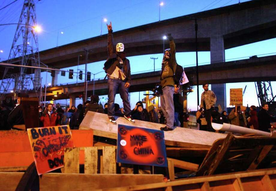 Occupy Seattle protesters stand atop a barricade on Monday, December 12, 2011 at the Port of Seattle. Hundreds of anti-Wall Street protesters gathered at the port and tried to shut down operations. Protesters scuffled with police during the rally and police used pepper spray and two flash-bang grenades to disperse the crowd after a protester threw a lit road flare toward officers. Another threw red paint on officers. Photo: JOSHUA TRUJILLO / SEATTLEPI.COM