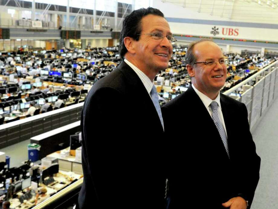Gov. Dan Malloy and UBS Americas Chief Executive Phil Lofts pose for photos above the trading room floor after a press conference in the UBS building in Stamford, Conn. on Tuesday, August 23, 2011. UBS committed to staying in Stamford for five years, in exchange for a generous package of incentives. Photo: Lindsay Niegelberg / Stamford Advocate