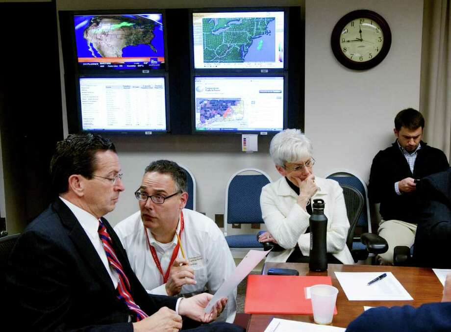 Gov. Dan Malloy is briefed by a CL&P representative as he and Lt. Gov. Nancy Wyman meet with federal and local officials in the Connecticut Department of Emergency Management and Homeland Security in Hartford, Conn., November 1, 2011 to discuss the response after an unseasonal snow storm. As power outages stretched into a full week, Malloy grew furious at the utilities and the federal government. Photo: Keelin Daly / Stamford Advocate