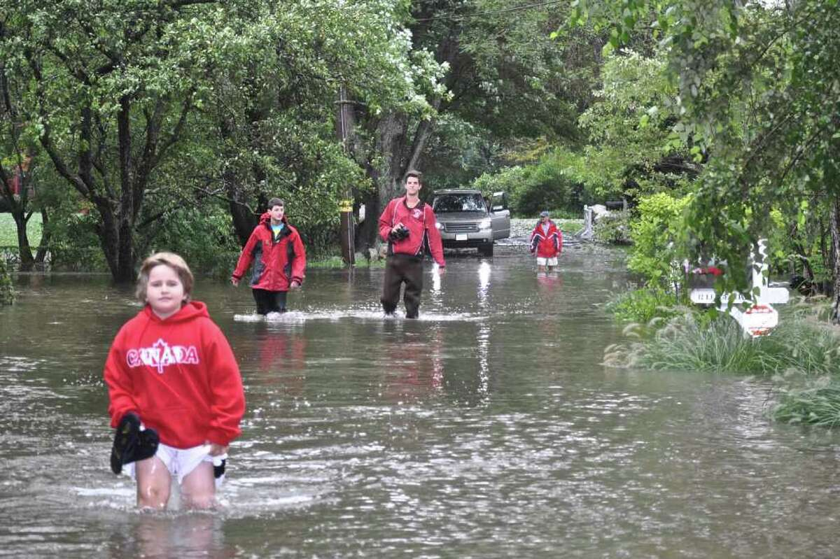 Residents of Ledge Road in Old Greenwich make their way through knee-deep water, a reminder of Irene's fury.