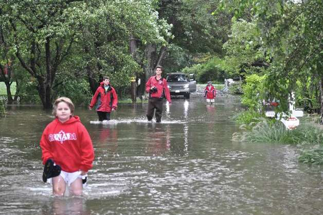 Residents of Ledge Road in Old Greenwich make their way through knee-deep water, a reminder of Irene's fury. Photo: Contributed Photo