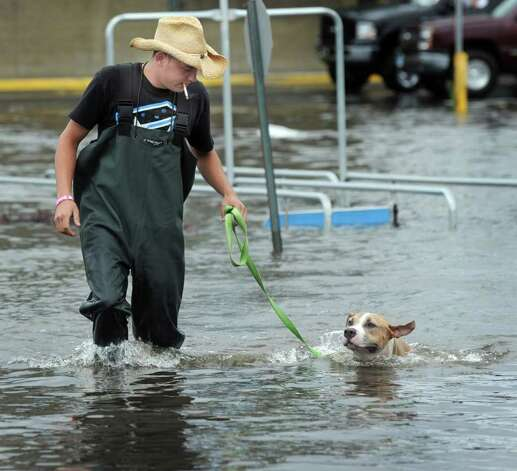 "Jeremiah Burke of Bethel took his friends dog for "" a swim"" he says, in the flooded Walmart parking lot in Danbury Sunday afternoon. Tropical Storm Irene brought heavy rain and winds to Greater Danbury Sunday. Photo taken Sunday, Aug. 28, 2011. Photo: Carol Kaliff"