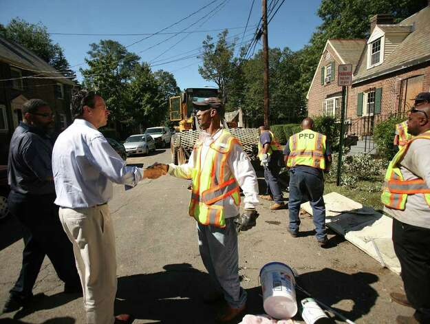 Governor Dannel P. Malloy, left, greets Bridgeport Public Works worker Ron Perry, cleaning up the Seaside Village neighborhood in the aftermath of Hurricane Irene, on Tuesday, August 30, 2011. Photo: Brian A. Pounds / Connecticut Post