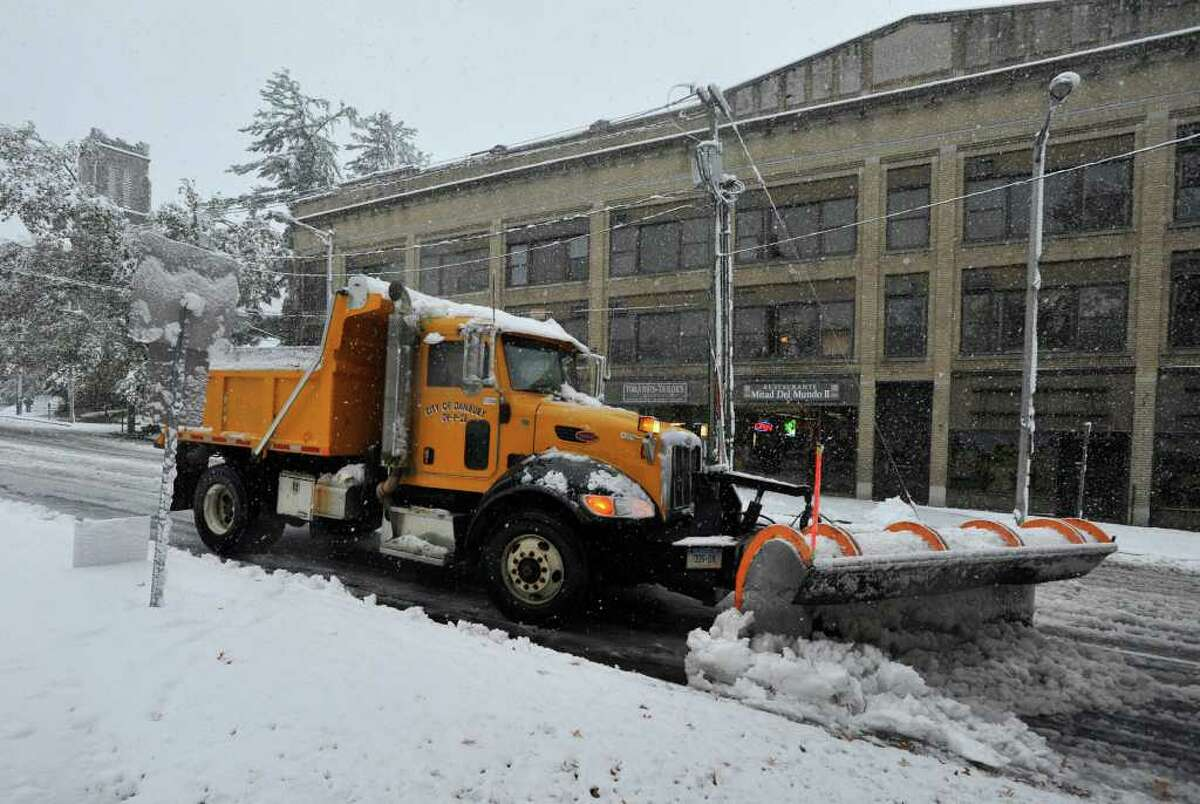 A city plow pushes snow along West Street in Danbury on Saturday, Oct. 29, 2011.