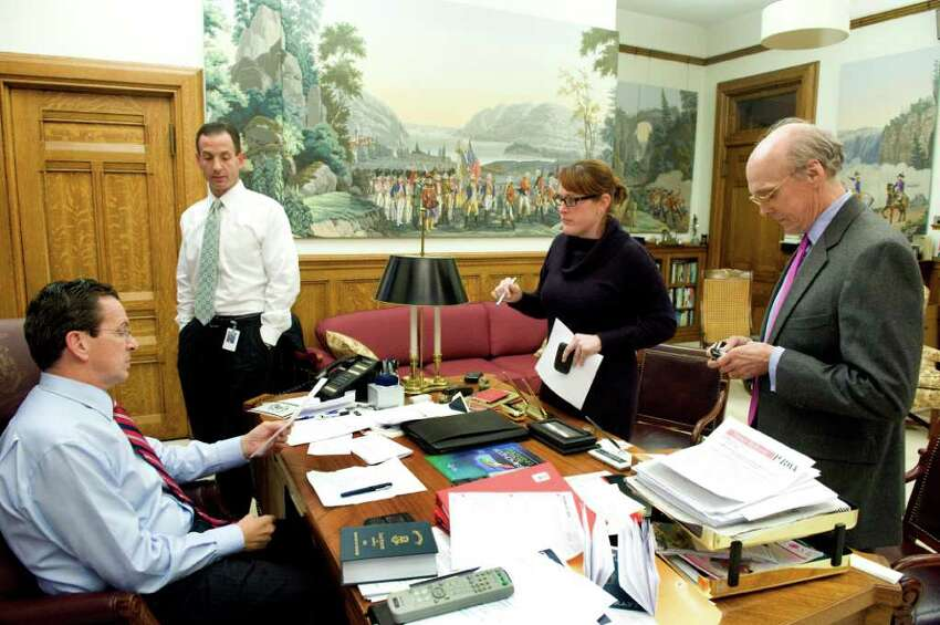 Gov. Dan Malloy meets with Roy Ochiogrosso, Colleen Flanagan and Tim Bannon in his office before heading to the televised signing of the jobs bill in Hartford, Conn., October 27, 2011.