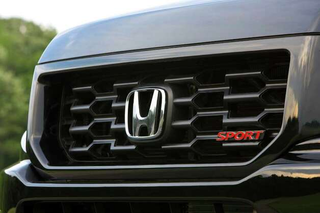 "This black honeycomb grille and red ""Sport"" badge are among the unique features of the new Ridgeline model. COURTESY OF AMERICAN HONDA MOTOR CO. Photo: American Honda Motor Co., COURTESY OF AMERICAN HONDA MOTOR CO. / Honda"