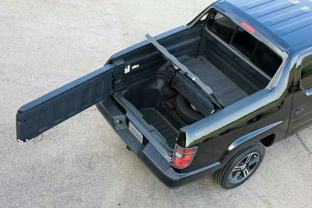 The 2012 Honda Ridgeline half-ton pickup features an exclusive in-bed trunk, and a tailgate that swings out to the side or lowers flat to the rear. COURTESY OF AMERICAN HONDA MOTOR CO. Photo: American Honda Motor Co., COURTESY OF AMERICAN HONDA MOTOR CO. / Honda
