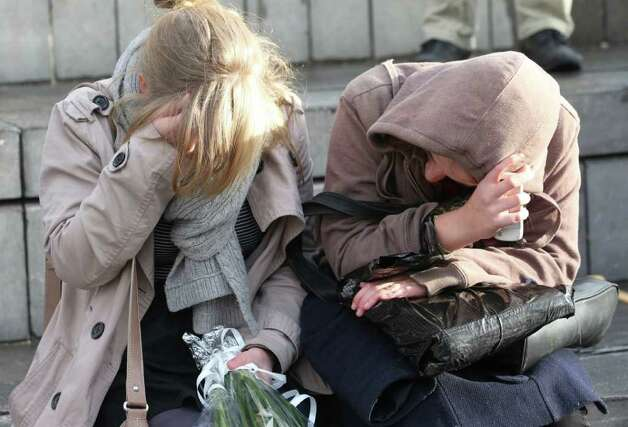 Women mourn as they sit at a bus stop where a grenade-lobbing gunman killed four people and injured 123, in the city center of Liege, Belgium, on Wednesday.  (AP Photo/Yves Logghe) Photo: Yves Logghe, ASSOCIATED PRESS / AP2011