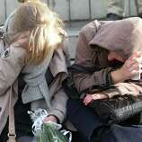 Women mourn as they sit at a bus stop where a grenade-lobbing gunman killed four people and injured 123, in the city center of Liege, Belgium, on Wednesday.  (AP Photo/Yves Logghe)