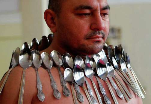 Etibar Elchiyev demonstrates his magnetic ability as he poses with 50 metal spoons magnetized to his body during an attempt to break the Guinness World Record for Most Spoons on a Human Body in Tbilisi, Georgia, on Wednesday. Elchiyev claims that his body acts as a magnet attracting metal objects. (AP Photo/Shakh Aivazov) Photo: Shakh Aivazov, ASSOCIATED PRESS / AP2011