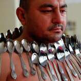 Etibar Elchiyev demonstrates his magnetic ability as he poses with 50 metal spoons magnetized to his body during an attempt to break the Guinness World Record for Most Spoons on a Human Body in Tbilisi, Georgia, on Wednesday. Elchiyev claims that his body acts as a magnet attracting metal objects. (AP Photo/Shakh Aivazov)