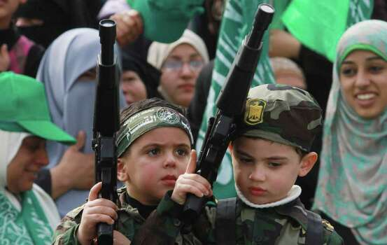 Palestinian children hold toy guns during a rally to mark 24 years of Hamas's founding, in Gaza city, on Wednesday.  Tens of thousands of Gazans turned out Wednesday for an anniversary rally of the ruling Hamas, a demonstration of strength for the Islamic militant movement ahead of Palestinian general elections tentatively set for the spring.  (AP Photo/Hatem Moussa) Photo: Hatem Moussa, ASSOCIATED PRESS / AP2011