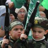 Palestinian children hold toy guns during a rally to mark 24 years of Hamas's founding, in Gaza city, on Wednesday.  Tens of thousands of Gazans turned out Wednesday for an anniversary rally of the ruling Hamas, a demonstration of strength for the Islamic militant movement ahead of Palestinian general elections tentatively set for the spring.  (AP Photo/Hatem Moussa)