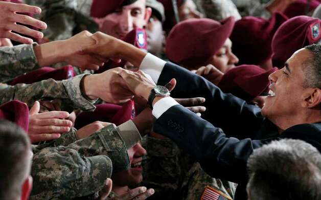 President Barack Obama greets members of the military at the 440th Structural Maintenance Hangar at Fort Bragg, N.C., on Wednesday. He saluted the troops in an adress. Photo: AP
