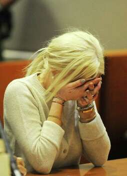 Lindsay Lohan covers her face during a progress report session at the Los Angeles Superior Court on Wednesday. A judge says Lohan is doing well under her strict new probation routine of counseling and working at the county morgue. Lohan remains on probation for a 2007 drunken driving and a grand theft case filed earlier this year. Photo: AP