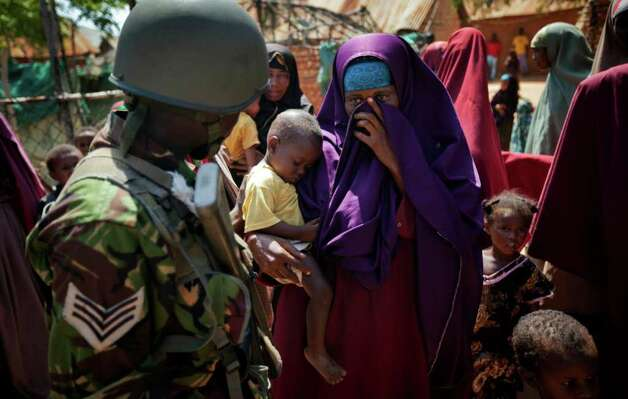 A Somali woman holds her baby who needs treatment, as she talks to a Kenyan army soldier outside a medical clinic where they were examining patients, in the seaside town of Bur Garbo, Somalia, on Wednesday.  (AP Photo/Ben Curtis) Photo: Ben Curtis, ASSOCIATED PRESS / AP2011