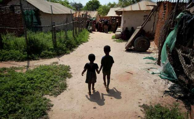 Two children walk hand-in-hand towards a clinic where a Kenyan army medic was examining patients, in the seaside town of Bur Garbo, Somalia, on Wednesday. The Kenyan military clearly realises that the ultimate success of their mission in Somalia depends on improving the lives of residents there but equally clear is that they did not plan on having to do it all themselves, leaving Somalis in Bur Garbo dependent on handouts from them. (AP Photo/Ben Curtis) Photo: Ben Curtis, ASSOCIATED PRESS / AP2011