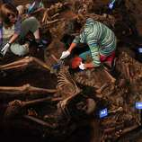 In this picture taken Monday and released by Argentine judicial officials Wednesday, forensic anthropologists work on a common grave recently discovered and allegedly containing the remains of at least 15 people apparently slain during the country's  1976-1983 dictatorship, in Argentina's northern state of Tucuman.