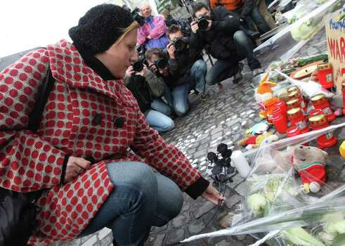 A woman lays black roses at a bus stop where a grenade-lobbing gunman killed four people and injured 123, in the city center of Liege, Belgium, on Wednesday. (AP Photo/Yves Logghe) Photo: Yves Logghe, ASSOCIATED PRESS / AP2011