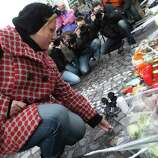 A woman lays black roses at a bus stop where a grenade-lobbing gunman killed four people and injured 123, in the city center of Liege, Belgium, on Wednesday. (AP Photo/Yves Logghe)