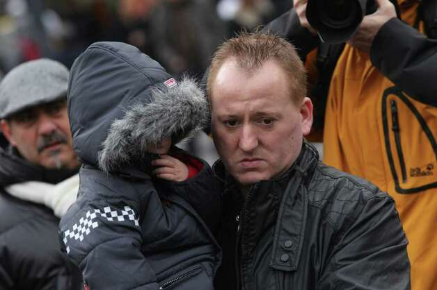 A father and his son mourn as they look at the scene Tuesday's attack in the city center of Liege, Belgium, on Wednesday. The body of a woman has been found in the garage of a grenade-lobbing gunman, bringing to four the number of people killed in an attack in the city of Liege, officials said Wednesday. (AP Photo/Yves Logghe) Photo: Yves Logghe, ASSOCIATED PRESS / AP2011