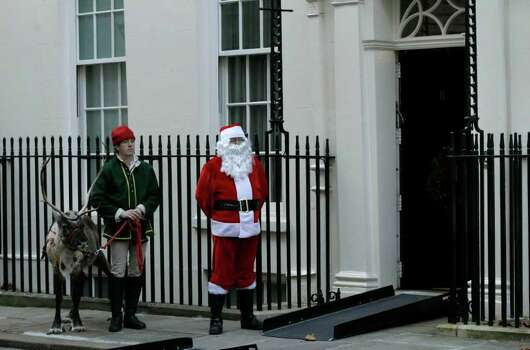 A man dressed as Father Christmas stands with a reindeer and handler outside 11, Downing Street, London, before the Chancellor of the Exchequer's annual Christmas party, Wednesday. Photo: Matt Dunham, AP / AP