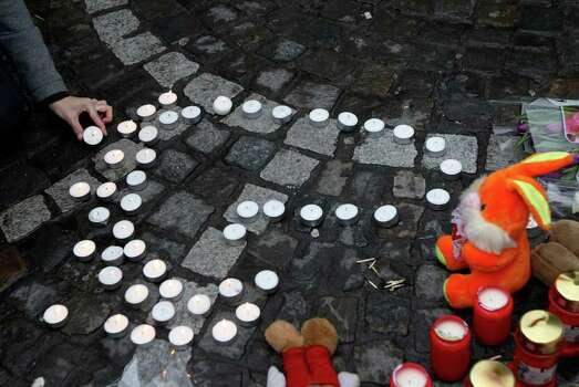 A woman light a candle at a bus stop where a grenade-lobbing gunman killed four people and injured 123, in the city center of Liege, Belgium, Wednesday. (AP Photo/Yves Logghe) Photo: Yves Logghe, ASSOCIATED PRESS / AP2011