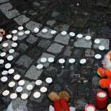 A woman light a candle at a bus stop where a grenade-lobbing gunman killed four people and injured 123, in the city center of Liege, Belgium, Wednesday. (AP Photo/Yves Logghe)