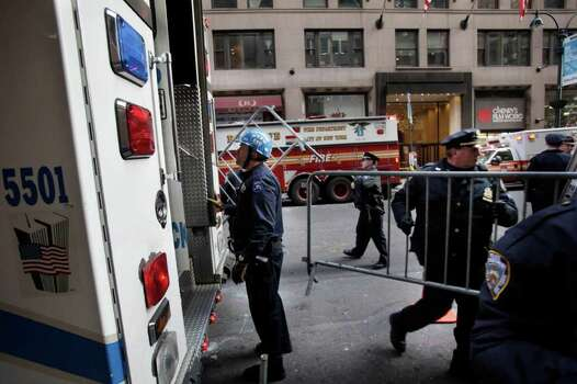 Emergency personnel gather outside of a building where there was an elevator accident in New York on Wednesday. A woman was killed when her foot or leg became caught in an elevator's closing doors, New York City fire officials said. Photo: AP