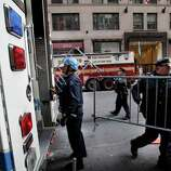 Emergency personnel gather outside of a building where there was an elevator accident in New York on Wednesday. A woman was killed when her foot or leg became caught in an elevator's closing doors, New York City fire officials said.