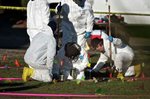 In a Tuesday photo, investigators work in the back yard of 591 N.E. 22nd Ave in Canby, Ore., where a an explosion caused by a pipe bomb inside a box killed one person over the weekend. Ivan Rodriguez, 31, died Sunday night when the bomb exploded in a toolbox-like container that he either poked or picked up as he was helping a family move out of their house, police said. Police were trying to determine whether the device was among belongings of the family, who were in the middle of a move to Salem. The explosion was being investigated by the Metro Explosive Disposal unit, which includes police in the Portland agency and federal agencies. (AP Photo/The Oregonian, Benjamin Brink) Photo: AP