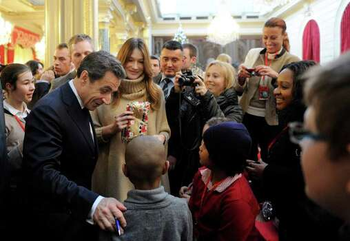 French President Nicolas Sarkozy, left, and his wife, Carla Bruni-Sarkozy, second left, give Christmas gifts to children during the traditional Christmas party at the Elysee Palace in Paris, Wednesday. Photo: Eric Feferberg, AP / AFP Pool