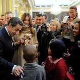 French President Nicolas Sarkozy, left, and his wife, Carla Bruni-Sarkozy, second left, give Christmas gifts to children during the traditional Christmas party at the Elysee Palace in Paris, Wednesday.