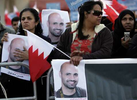 "Anti-government protesters, including nurse Rula al-Saffar, left, hold Bahraini flags and pictures of jailed nurse and photographer Hasan Matooq during a rally Wednesday outside the United Nations offices in Manama, Bahrain. Protest leaders delivered a letter to U.N. officials saying they demand an elected government and seeking U.N. monitoring of the government response to an international investigation that found numerous human rights abuses. The sign, held by al-Saffar who is among medical workers being retried on charges relating to the uprising, reads:""Freedom for the angel of mercy, the nurse Hasan Matooq."" Photo: Hasan Jamali, AP / AP"