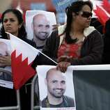 "Anti-government protesters, including nurse Rula al-Saffar, left, hold Bahraini flags and pictures of jailed nurse and photographer Hasan Matooq during a rally Wednesday outside the United Nations offices in Manama, Bahrain. Protest leaders delivered a letter to U.N. officials saying they demand an elected government and seeking U.N. monitoring of the government response to an international investigation that found numerous human rights abuses. The sign, held by al-Saffar who is among medical workers being retried on charges relating to the uprising, reads:""Freedom for the angel of mercy, the nurse Hasan Matooq."""