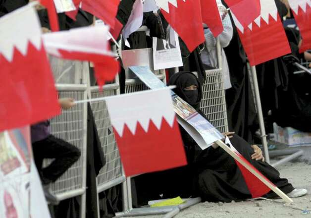 Anti-government protesters wave Bahraini flags during a rally Wednesday outside the United Nations offices in Manama, Bahrain. Photo: Hasan Jamali, AP / AP