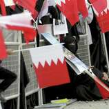 Anti-government protesters wave Bahraini flags during a rally Wednesday outside the United Nations offices in Manama, Bahrain.