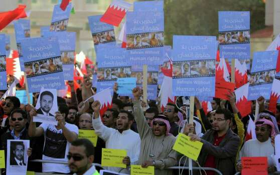 Tens of thousands of Bahraini anti-government protesters wave Bahraini flags, carry signs and shout slogans against the monarchy on Wednesday. Photo: Hasan Jamali, AP / AP