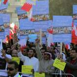 Tens of thousands of Bahraini anti-government protesters wave Bahraini flags, carry signs and shout slogans against the monarchy on Wednesday.