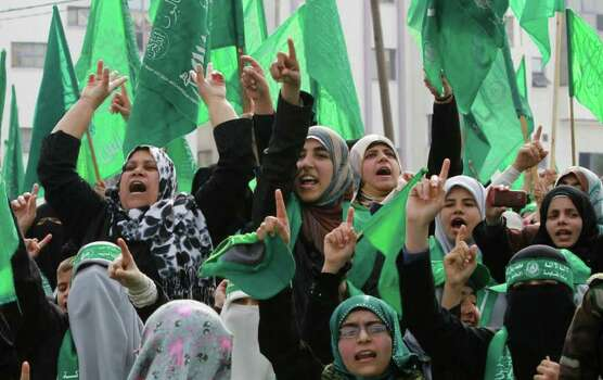 Palestinian women gather during a rally to mark 24 years since Hamas' founding, in Gaza city, on Wednesday. , Dec. 14, 2011.  Tens of thousands of Gazans turne  (AP Photo/Hatem Moussa) Photo: Hatem Moussa, ASSOCIATED PRESS / AP2011