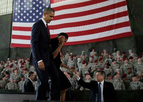 President Barack Obama and first lady Michelle Obama leave the stage to greet members of the military at Fort Bragg, N.C., on Wednesday. Photo: AP