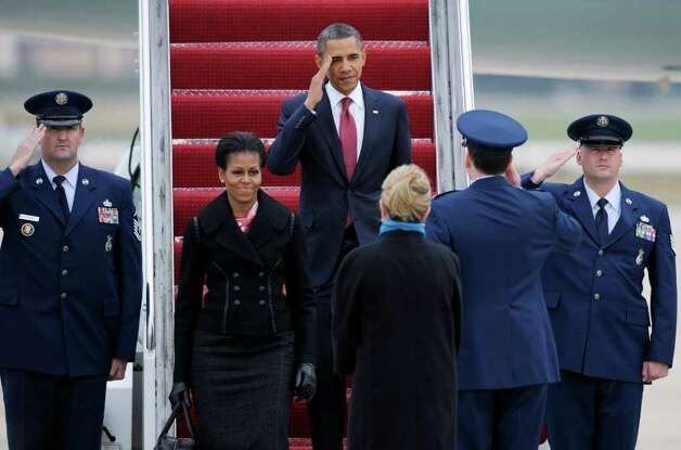 President Barack Obama, accompanied by first lady Michelle Obama, salutes an Air Force officer as they walk down the stairs of Air Force One at Andrews Air Force Base, Md., on Wednesday. Photo: AP