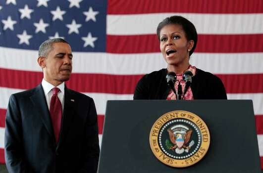 President Barack Obama listens as first lady Michelle Obama speaks to troops at Fort Bragg, N.C., on Wednesday. Photo: AP