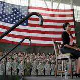 First lady Michelle Obama listens as President Barack Obama speaks to troops at Fort Bragg, N.C., on Wednesday.