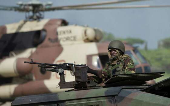A Kenyan army soldier on an armored vehicle keeps watch in front of a Kenyan air force helicopter at their base near the seaside town of Bur Garbo, Somalia, on Wednesday. Photo: Ben Curtis, AP / AP