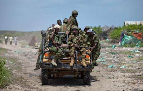 Kenyan army soldiers, wearing helmets, and members of a pro-government Somali militia ride on a truck in the seaside town of Bur Garbo, Somalia, on Wednesday. Photo: Ben Curtis, AP / AP