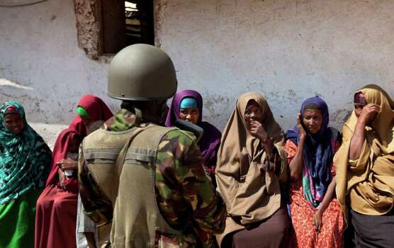 Somali women speak to a Kenyan army soldier as they wait to seek treatment outside a medical clinic where a Kenyan army medic was examining patients, in the seaside town of Bur Garbo, Somalia, on Wednesday. Photo: Ben Curtis, AP / AP