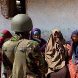 Somali women speak to a Kenyan army soldier as they wait to seek treatment outside a medical clinic where a Kenyan army medic was examining patients, in the seaside town of Bur Garbo, Somalia, on Wednesday.