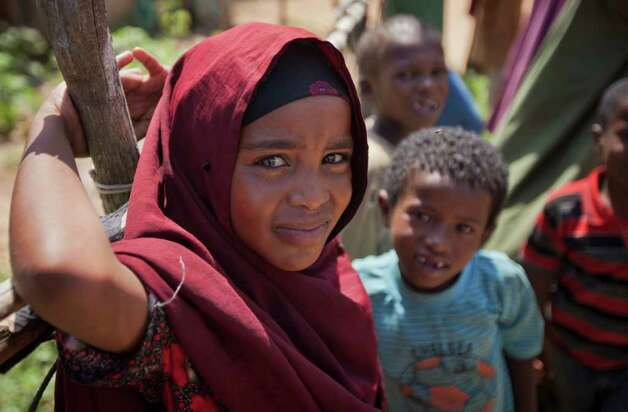 A young Somali girl stands with other children watching the commotion as residents queue up to seek treatment at a medical clinic where a Kenyan army medic was examining patients, in the seaside town of Bur Garbo, Somalia, on Wednesday.  (AP Photo/Ben Curtis) Photo: Ben Curtis, ASSOCIATED PRESS / AP2011